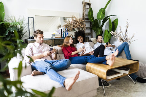 Friends sitting on couch, working casually together, using smartphones - GIOF06109