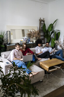 Friends sitting on couch, working casually together, using - GIOF06118