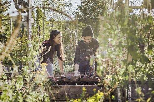 Happy couple gardening in urban garden together - VGPF00002