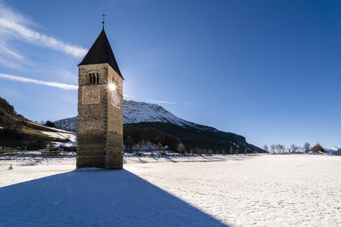 Italy, Venosta Valley, Sunken spire in frozen Lago di Resia in winter - STSF01905
