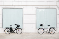 Two e-bikes at a white wall with two windows - JRFF02899