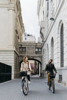 Smiling couple riding e-bikes in the city - JRFF02902