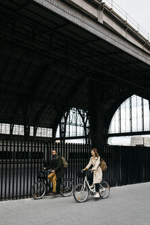 Couple riding e-bikes in the city - JRFF02905