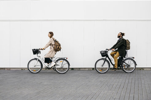 Couple riding e-bikes along a white wall in the city - JRFF02908