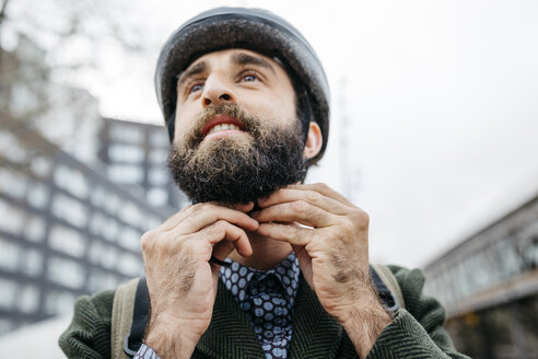 Portrait of man putting on bicycle helmet in the city - JRFF02917