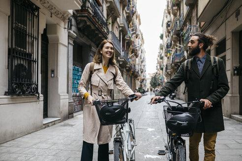 Couple pushing e-bikes exploring the city - JRFF02920