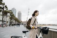 Woman with e-bike having a break on beach promenade - JRFF02938