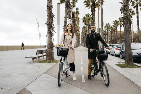 Portrait of couple with e-bikes on a promenade - JRFF02941