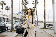 Portrait of smiling woman with e-bike on a promenade - JRFF02944