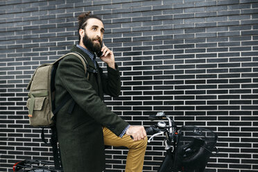 Man with e-bike talking on cell phone at a brick wall - JRFF02956