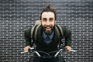 Portrait of happy man with e-bike at a brick wall - JRFF02962
