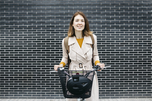 Portrait of smiling woman with e-bike at a brick wall - JRFF02965