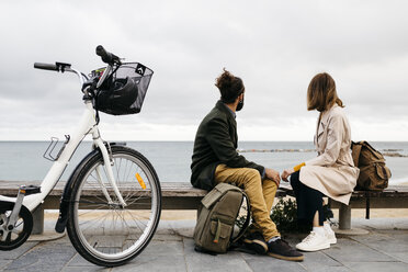 Couple sitting on a bench at beach promenade next to e-bike looking at the sea - JRFF02968