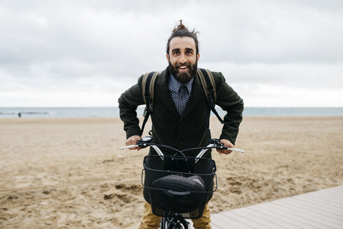 Portrait of happy man with e-bike at the beach - JRFF02977