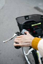 Close-up of woman on e-bike connecting the electric motor - JRFF02980