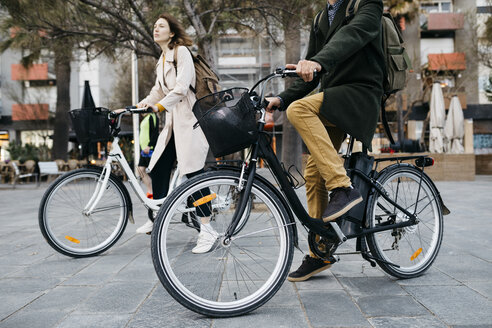 Couple riding e-bikes in the city - JRFF02983