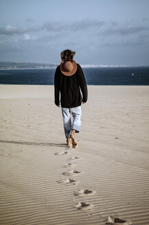 Young man walking away in the dunes, rear view - OCMF00362