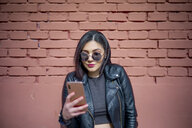 Portrait of young woman wearing sunglasses and black leather jacket looking at smartphone - OCMF00371