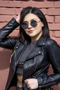 Portrait of young woman wearing sunglasses and black leather jacket - OCMF00374