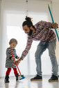 Happy father and little daughter sweeping the floor of the living room at home - JRFF02985