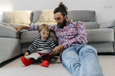 Father and little daughter sitting in the floor in the living room reading a book together - JRFF02988