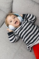 Portrait of toddler girl lying on the couch listening music with headphones - JRFF02991