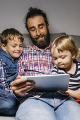Portrait of father sitting on the couch with his children watching movies on digital tablet - JRFF03015