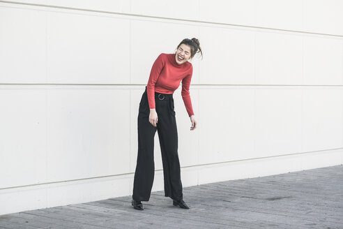 Laughing young woman standing in front of a wall - UUF17050