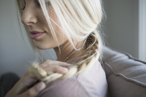 Close up blonde young woman holding braid - HEROF34863