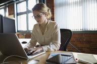 Businesswoman working at laptop at office desk - HEROF34905