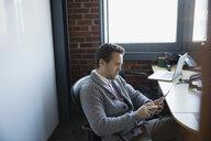 Businessman using digital tablet in office - HEROF34974