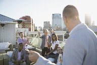 Businessman leading champagne toast on sunny urban rooftop - HEROF34989