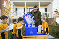 Coach and boys sports team gathering recycling neighborhood - HEROF34998