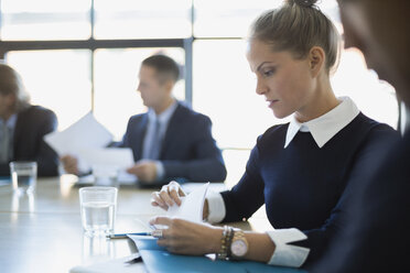 Businesswoman reviewing paperwork in conference room meeting - HEROF35016