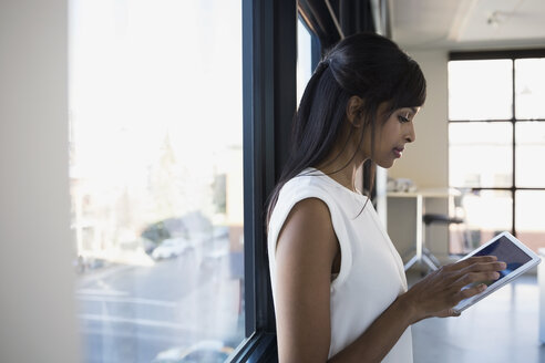 Businesswoman using digital tablet at office window - HEROF35055