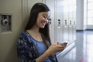 High school student texting at lockers - HEROF35130