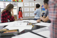 High school student teacher reviewing sketches art class - HEROF35169