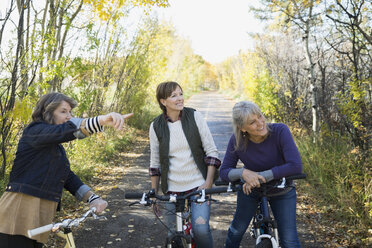Friends pointing on bicycles on autumn park path - HEROF35280