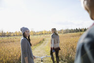 Friends with bicycle walking in sunny autumn field - HEROF35289