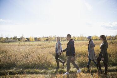 Friends walking in sunny autumn field - HEROF35292