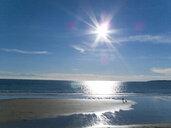 Woman and dog enjoying the sun, beach and ocean at Gerrans Bay, Cornwall, United Kingdom - JUIF00843