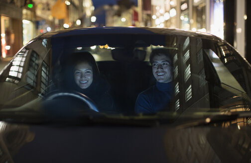 Smiling couple driving on city street - HOXF04322