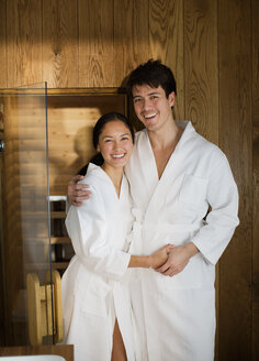Portrait happy couple in bathrobes at spa - HOXF04331