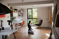 Young woman meditating on floor in home office - HOXF04370