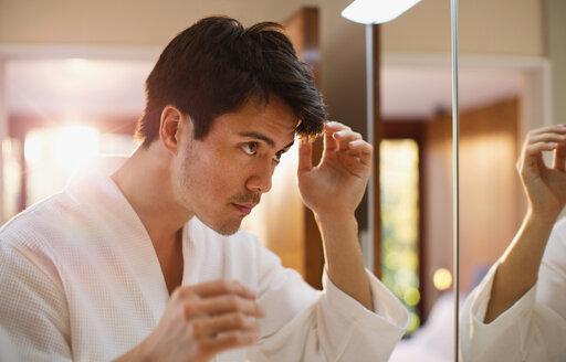Man checking hair in bathroom mirror - HOXF04397