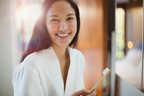 Portrait happy young woman brushing teeth in bathroom - HOXF04400
