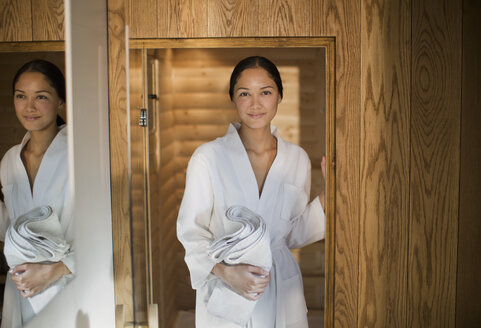 Portrait young woman in bathrobe standing in spa doorway - HOXF04406