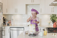 Smiling girl decorating cake in kitchen - CAIF23057