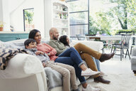 Family watching TV on living room sofa - CAIF23111