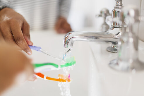 Close up family rinsing toothbrushes in bathroom sink - CAIF23144